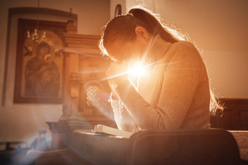 Christian woman praying in church. Hands crossed and Holy Bible on wooden desk. Wall mural