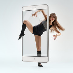 Portrait of young graceful woman performing contemporary dance, concept virtual reality of the smartphone. going out of the device