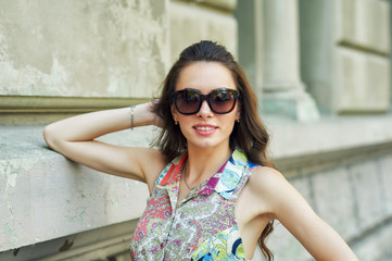 Portrait of a young beautiful fashionable woman on a city street wearing sunglasses .