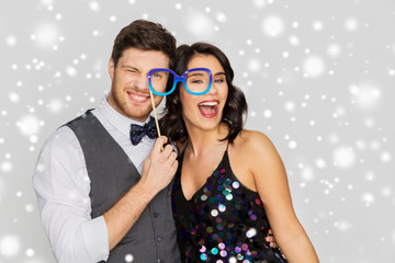 fun and holidays concept - happy couple posing with party props over grey background and snow