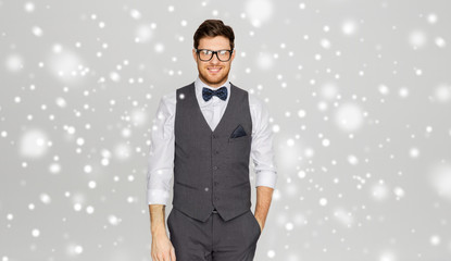 fashion, vintage style and winter concept - happy man in festive suit and eyeglasses over grey background and snow