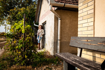Beautiful curly woman standing next to a house on brown leaves during autumn on a vineyard