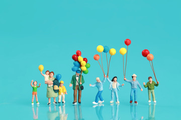 Miniature people: a group of happy family are having fun and holding balloon use as background.