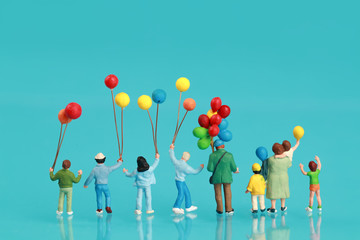 Miniature people: back view of a group of happy family are having fun and holding balloon use as background
