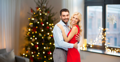 love and holidays concept - happy couple hugging over home room with christmas tree background