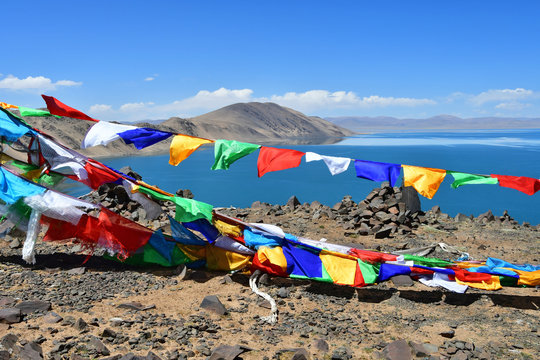 Tibet, Buddhist flags with mantras on Nam-Tso lake background (Nam Tso) on a cloudy summer day