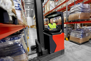 logistic business, shipment and loading concept - male loader operating forklift at warehouse