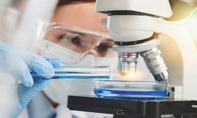 Young Female Scientist Working with Microscope