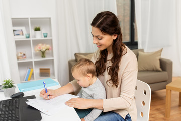 motherhood, multi-tasking, family and people concept - happy mother with baby, papers and laptop working at home