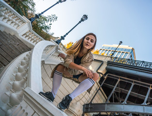 Outdoor autumn lifestyle image of a young pretty chestnut haired caucasian girl having fun and dancing on the street on the staircase. Cute casual outfit in front of building.