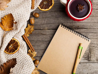 Mulled wine in a cup in a case and a notebook. Leaves, knitted blanket, dry orange, cinnamon and acorns on an old wooden table, copy Space, Fall.
