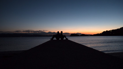 A couple sit back to back on a sea pier at sundown to create a beautiful romantic photo. The 2 people are silhouetted against a sunset sky and a calm ocean.