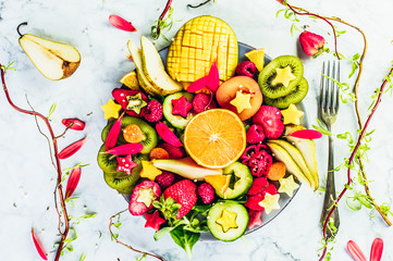 Colourful fresh fruit platter with strawberries, mango, kiwis and pears on white background