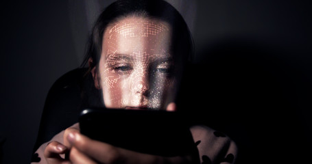 Young girl having her face scanned by her smart phone. Facial recognition concept