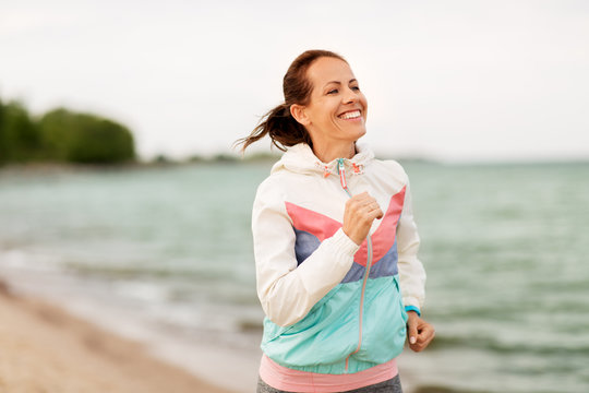 fitness, sport and healthy lifestyle concept - smiling woman running along beach