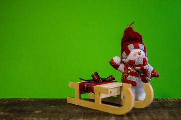 Closeup of snowman with a red scarf and white scarf throwing a snowball and a snowsled