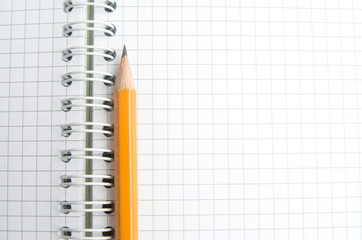 The pencil is on the notebook of the student. Close up.