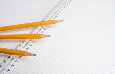 Three pencils lie on a notebook sheet.