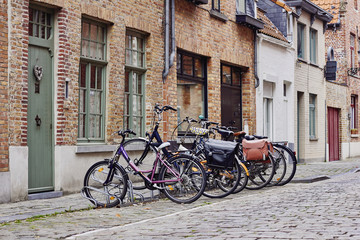 Traditional medieval town. Narrow paved street with old brick houses and bikes near entrance
