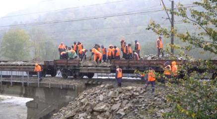A still image taken from a video footage shows emergency service workers unloading stones on a railway bridge following a recent flood in Krasnodar Region