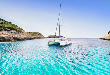 Beautiful bay with sailing boat catamaran, Corsica island, France