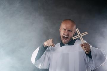 Catholic priest exorcist in white surplice and black shirt