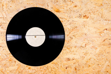 Black color vinyl record on plywood background
