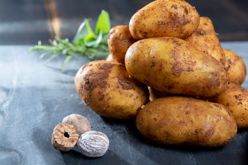 New harvest potatoes not washed with soil on table with nutmeg