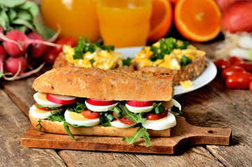 Baguette sandwich with egg, arugula salad, tomatoes and radish