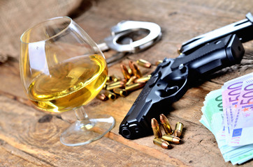 Glass of cognac, 9mm pistol handgun, handcuffs, bullets and euro banknotes on old wooden table