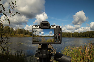 A camera standing on a tripod and taking a picture of a landscape with a lake, landing and clouds