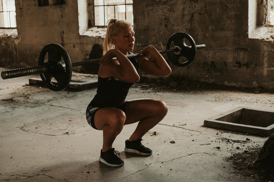 Athletic woman doing front squat in an old building