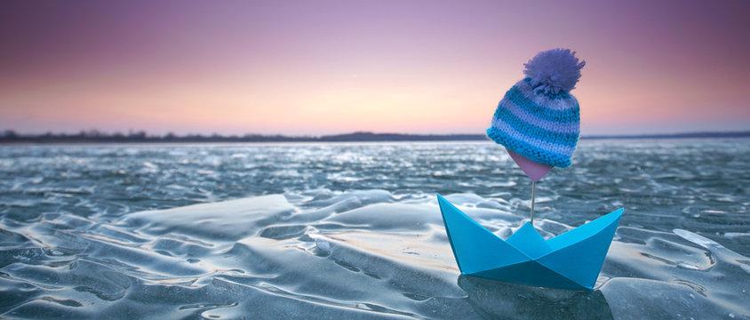 Eisschollen und Papierboot am See