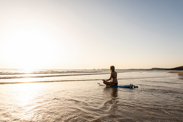Young woman practicing yoga on the beach, sitting on surfboard, meditating