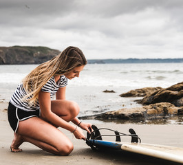 Blond young woman preparing surfboard on beach