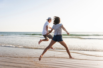 Young couple having fun on the beach, running and jumping at the sea
