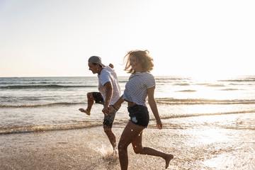 Young couple having fun at the beach, splashing water in the sea