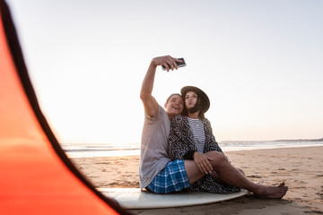 Couple camping on the beach, taking smartphone selfies