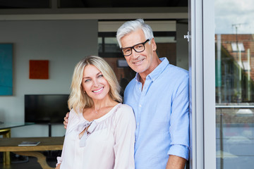 Portrait of smiling mature couple at the balcony at home