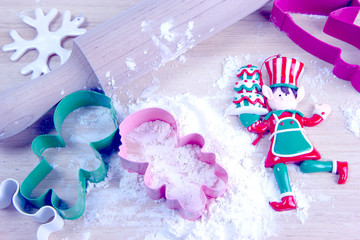 Flour, wooden rolling pin and cutting board, cookie cutters for a gingerbread man. Christmas and New Year holiday background concept. Copy space for text.