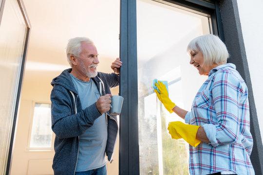 Bringing tea. Loving bearded blue-eyed husband feeling amazing while bringing some tea his wife cleaning doors