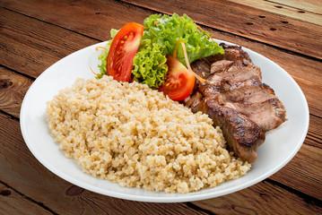 Millet porridge with pork grilled. On a wooden background