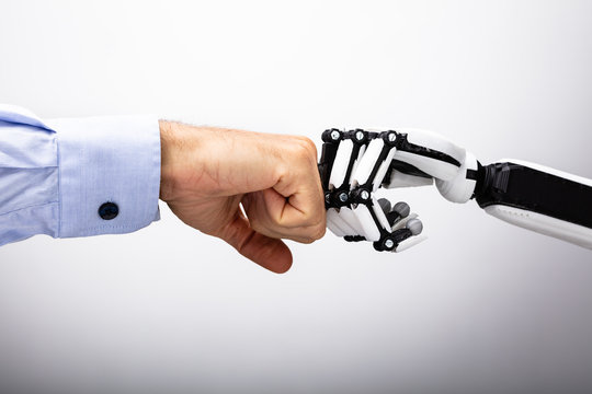 Human Hand And Robot Making Fist Bump