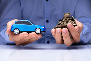 Man Holding Blue Car And Golden Coins