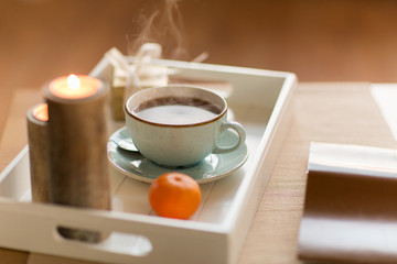 holidays and still life concept - cup of hot chocolate, christmas gift, mandarin and candles on table