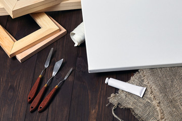 A white blank canvas on stretcher, palette knives, subframes, a tube with oil or acrylic paint and sackcloth lying on a brown wooden table