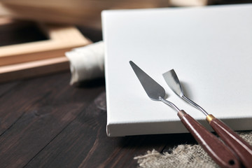 Artist tools: Palette knives lying on a white primed cotton canvas. wooden stretchers in the blurred background. Selective focus