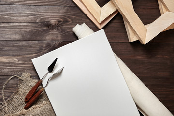 A white blank rectangular primed  canvas, roll, palette knives and stretchers lying on a brown wooden background. Top view