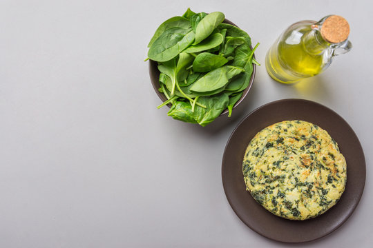 Homemade delicious potatoes eggs frittata with spinach on plate. Recipe ingredients olive oil in bottle on gray kitchen table. Dinner preparation. Overhead top view copy space