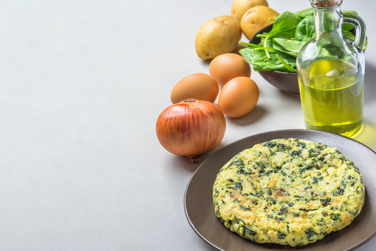 Homemade delicious potatoes eggs frittata with spinach on plate. Recipe ingredients onion olive oil in bottle on gray kitchen table. Rustic style. Copy space